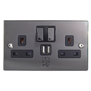a metallic black USB wall socket face plate with two UK mains female plug sockets on either side and two type A USB female sockets in the middle with two metallic black on and off switches